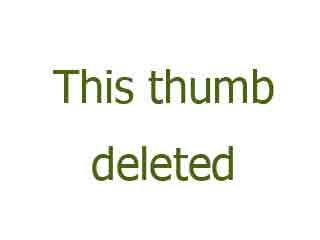 flexible brunette fucks herself in a doorway with a dildo